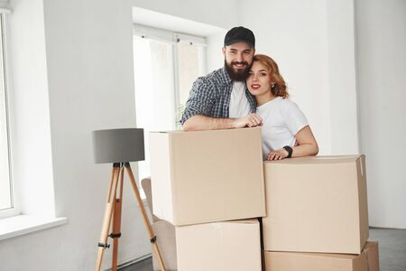 Near the windows. Happy couple together in their new house. Conception of moving.
