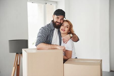 Embracing each other. Happy couple together in their new house. Conception of moving.