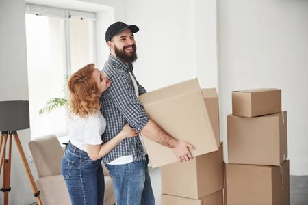 Side view. Happy couple together in their new house. Conception of moving. Stock Photo