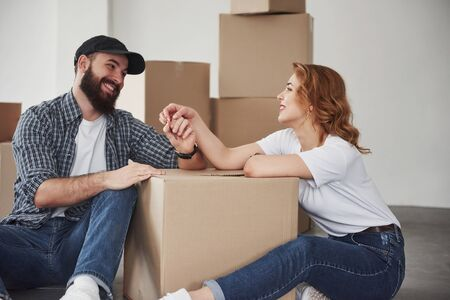 Joking around. Happy couple together in their new house. Conception of moving.