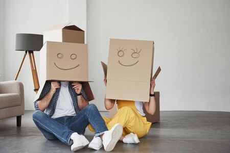 Smiley pictures on the boxes. Happy couple together in their new house. Conception of moving. Stock Photo