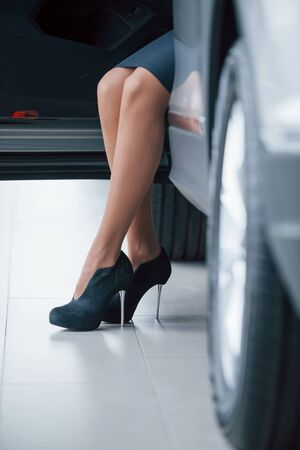 White floor. Cropped photo of woman in black high heels that sitting in the car. Stock Photo
