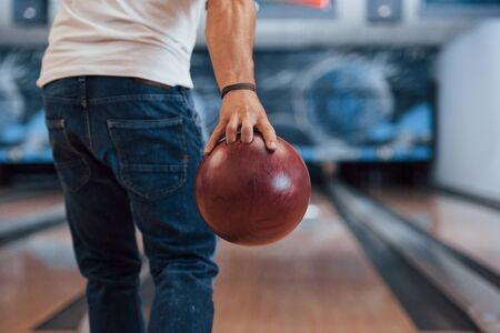 This is gonna be the strike. Rear particle view of man in casual clothes playing bowling in the club.