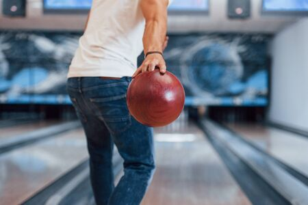 Weekend activities. Rear particle view of man in casual clothes playing bowling in the club. 스톡 콘텐츠