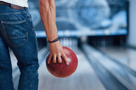 Strong hands. Rear particle view of man in casual clothes playing bowling in the club. 스톡 콘텐츠