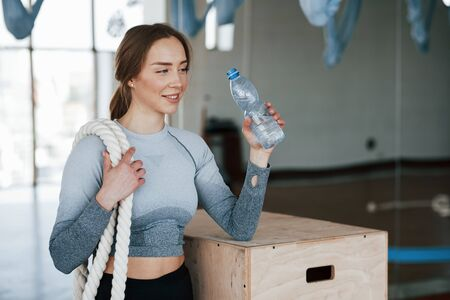 Holding bottle with water. Sportive young woman have fitness day in the gym at morning time.