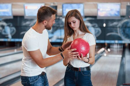 Man teaching girl how to holds ball and play bowling in the club. 版權商用圖片