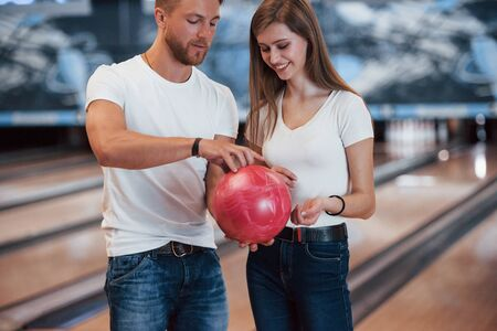 Hold it by that way. Man teaching girl how to holds ball and play bowling in the club. 版權商用圖片