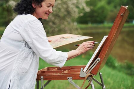 Positive woman. Portrait of mature painter with black curly hair in the park outdoors.