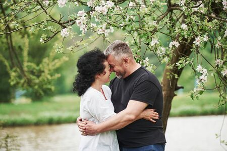 Smiling and embracing. Cheerful couple enjoying nice weekend outdoors. Good spring weather.