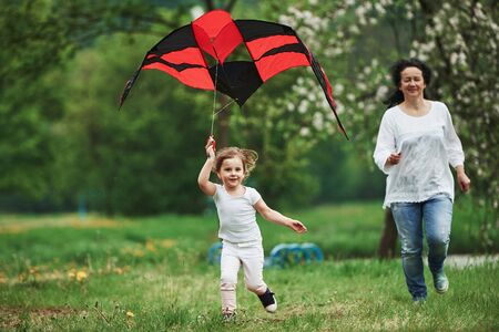 Fast and active. Positive female child and grandmother running with red and black colored kite in hands outdoors.