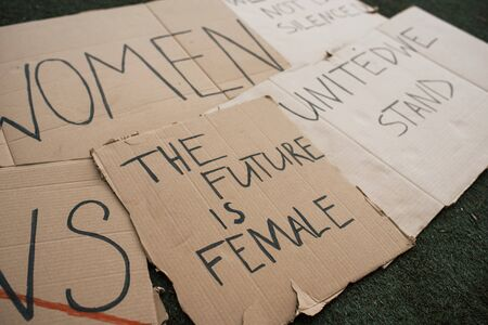 Handmade signs. Group of banners with different feminist quotes lying on the ground.