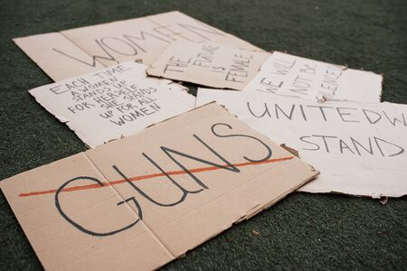 Say no to guns. Group of banners with different feminist quotes lying on the ground. Imagens