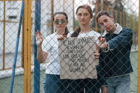 Quote on the paper. Group of feminist women have protest for their rights outdoors.