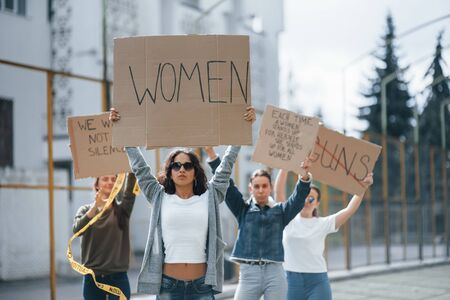 With hands up. Group of feminist women have protest for their rights outdoors.