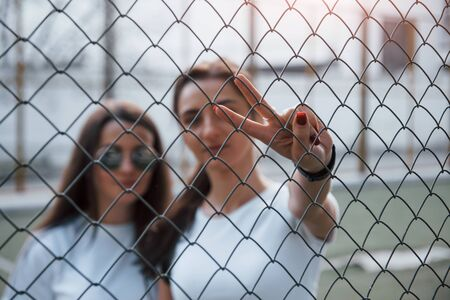 Two female friends stands behind the fence at daytime outdoors.