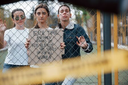 Through the fence. Group of feminist women have protest for their rights outdoors. Stok Fotoğraf