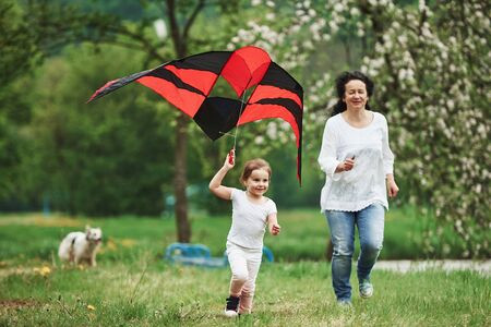 Dog is at background. Positive female child and grandmother running with red and black colored kite in hands outdoors.