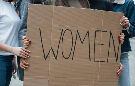 Holding big poster. Group of feminist women have protest for their rights outdoors.