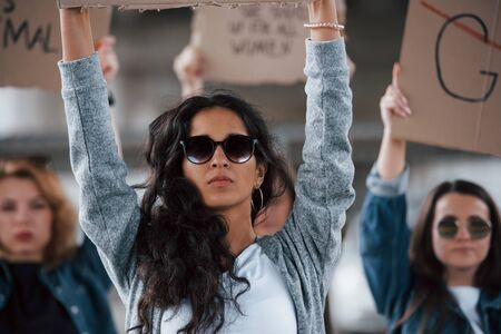 Luxury sunglasses. Group of feminist women have protest for their rights outdoors.