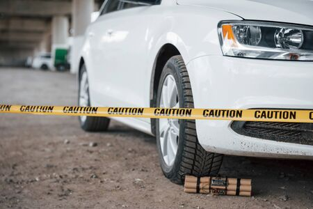 Be careful, its dangerous. Explosive near the wheel of modern white car. Yellow caution tape in front.