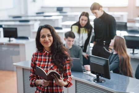 Brown colored book in hands. Group of young people in casual clothes working in the modern office.
