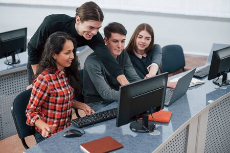 Everything will be awesome. Group of young people in casual clothes working in the modern office.