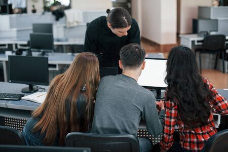 Together near one monitor. Group of young people in casual clothes working in the modern office. Zdjęcie Seryjne