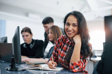 Cheerful brunette. Group of young people in casual clothes working in the modern office. Zdjęcie Seryjne