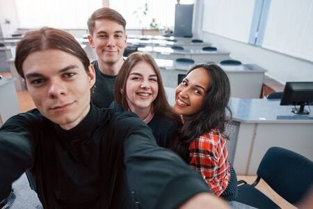 Taking a selfie. Group of young people in casual clothes working in the modern office.