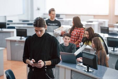 Using black colored smartphone. Group of young people in casual clothes working in the modern office.