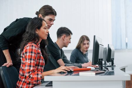 Am I doing it right. Group of young people in casual clothes working in the modern office.