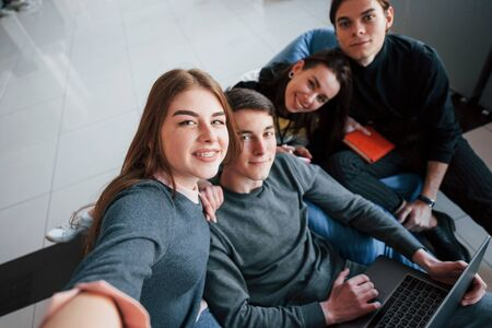 Smile to the camera. Group of young people in casual clothes working in the modern office.