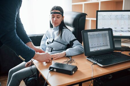 Trying not to worry. Girl passes lie detector in the office. Asking questions. Polygraph test. Фото со стока