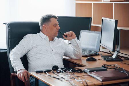 Mirando diagramas. El examinador de polígrafo trabaja en la oficina con su equipo de detectores de mentiras.