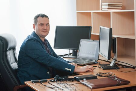In his own cabinet. Polygraph examiner works in the office with his lie detectors equipment.