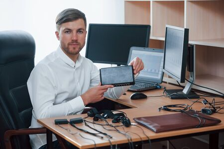 Young professional. Polygraph examiner works in the office with his lie detectors equipment.