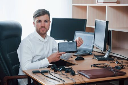 New equipment. Polygraph examiner works in the office with his lie detector.