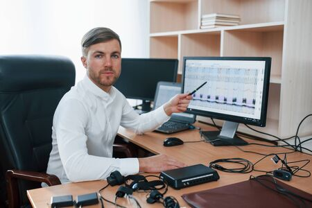 Looking into the camera. Polygraph examiner works in the office with his lie detectors equipment.