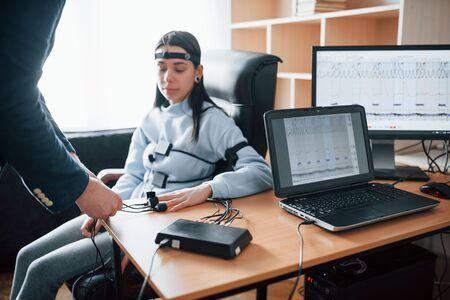 Preparación, poniendo electrodos en los dedos. Chica pasa detector de mentiras en la oficina. Haciendo preguntas. Prueba de polígrafo.