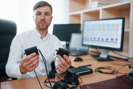 Debes usar estos dispositivos. El examinador de polígrafo trabaja en la oficina con su equipo de detectores de mentiras. Foto de archivo
