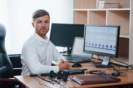 White shirt and many of devices. Polygraph examiner works in the office with his lie detectors equipment. Stok Fotoğraf