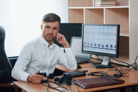 Everybody lies. Polygraph examiner works in the office with his equipment.