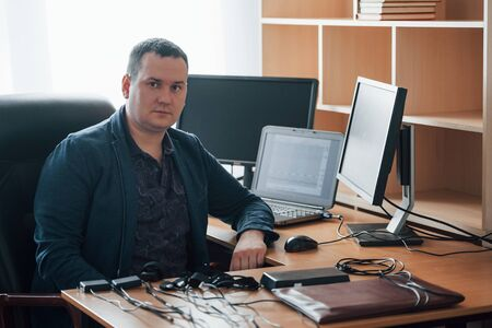 Portrait of professional polygraph examiner in the office with his lie detectors equipment.