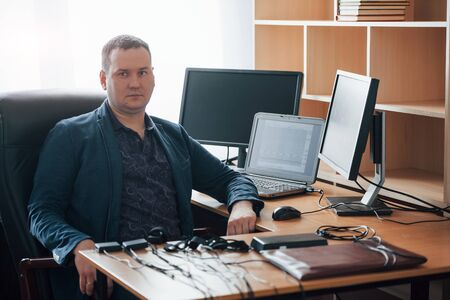 Sitting on the black chair. Polygraph examiner works in the office with his lie detectors equipment. Фото со стока