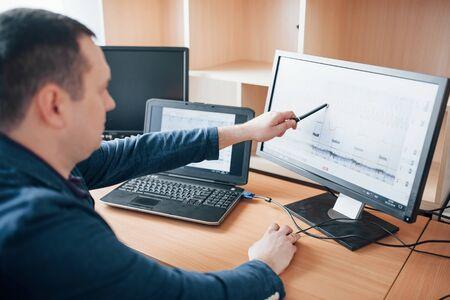 Spitzenwert der Kurve im Diagramm anzeigen. Polygraph-Prüfer arbeitet im Büro mit seiner Lügendetektor-Ausrüstung. Standard-Bild