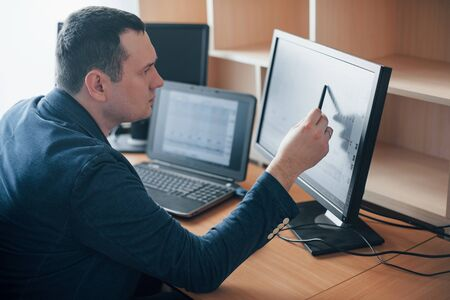 I see how man had worried at this moment. Polygraph examiner works in the office with his lie detectors equipment. Фото со стока