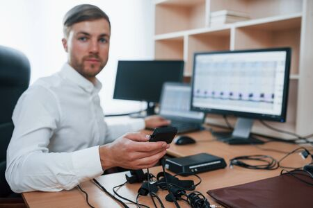 You can trust us. Polygraph examiner works in the office with his lie detectors equipment.