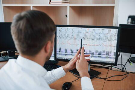 Arbeitsprozess. Polygraph-Prüfer im Büro mit der Ausrüstung seines Lügendetektors.