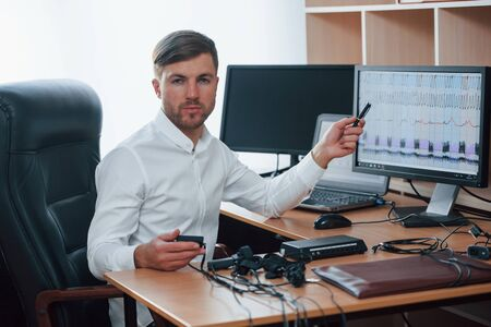Talking about results. Polygraph examiner works in the office with his lie detectors equipment.